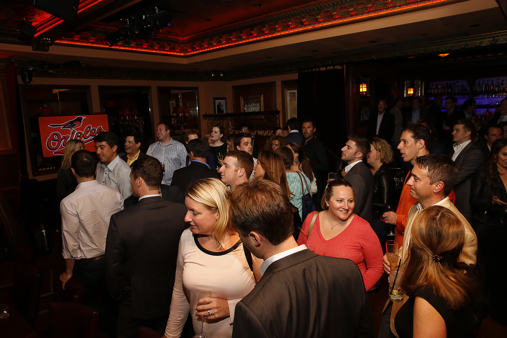 People mingle in dining room at Baltimore Orioles event